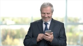 Elderly smiling businessman using smartphone. Cheerful older buinessman texting a message on his smartphone while standing on office background. People stock video footage