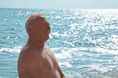 Elderly smiling man on seacoast royalty free stock photography