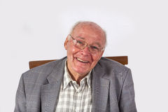 Elderly smiling man sitting on a chair Stock Image