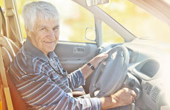 Elderly smiling man at the wheel. Autumn sunny day. Stock Photography