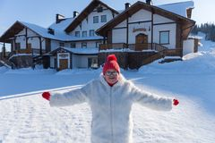 An elderly smiling woman stands with arms outstretched in front of the cottage, on a sunny winter day stock photo