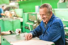 Elderly smiling worker looks in drawing Stock Photos