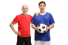 Elderly soccer player and young soccer player with football Royalty Free Stock Image