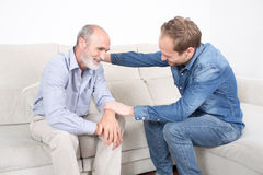 Elderly son comforting father Royalty Free Stock Photo