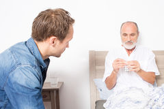 Elderly son gives medicine to his father Royalty Free Stock Images
