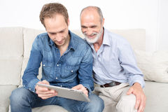 Elderly son with his father. Father and son looking at ipad device Stock Photos