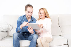 Elderly son with mother. Looking at ipad device Royalty Free Stock Photos