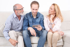 Elderly son shows something on a phone to his parents. Man at the psychoanalysis while psychologist looks at tablet Stock Photos