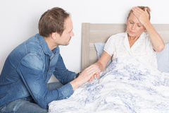 Elderly son takes care of ill mother in bed Royalty Free Stock Image