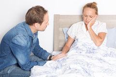 Elderly son takes care of ill mother in bed Stock Photos