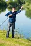 Elderly but still active man is fixing his rod. While preparing to go fishing. Man is standing on the green grass of the river bank. Unfocused forest and river stock photography