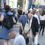 An elderly stooped man walking down the street through the crowd Royalty Free Stock Images