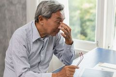 Elderly stress tired and holding his nose suffer sinus pain fatigue. Asian elderly stress tired and holding his nose suffer sinus pain fatigue from hard work royalty free stock photo