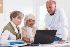 Elderly students sitting beside laptop Royalty Free Stock Image