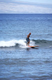 Elderly Surfer. Elderly gentleman out surfing on the blue waves royalty free stock image