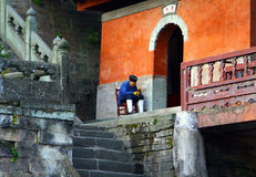 Elderly taoist monk sitting at the entrance to Purple Cloud Temple in Wudang Mountains, Hubei province Royalty Free Stock Image
