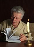 Elderly thoughtful man with book Royalty Free Stock Photography