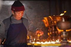 Elderly Tibetan watching butter lamps. On March 9, 2017, Kathmandu. Nepal. stock photos