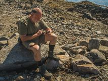 Elderly tired man sitting on the big stone on the coast using hi. Senior man hiker searching a route, using his phone, view from above, stone background royalty free stock photos