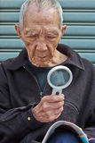 The elderly to read with a magnifying glass Stock Photography