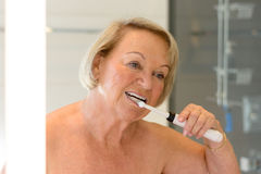 Elderly topless lady cleaning her teeth Royalty Free Stock Photos
