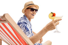 Elderly tourist with a cocktail sitting on a sun lounger Stock Photos