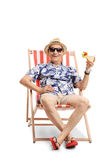 Elderly tourist with a cocktail sitting in a sun lounger Stock Image