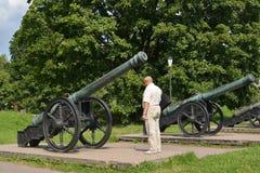 The elderly tourist examines XVIII century guns. St. Petersburg Stock Image