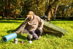 Elderly tourist foldjng a tent in the forest Stock Images