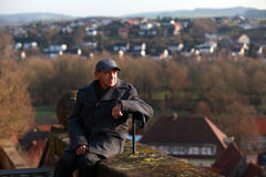 Elderly tourist in a historic town. Senior man relaxing and enjoying the view of a historic town in Germany stock photo