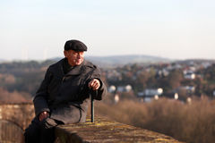 Elderly tourist in a historic town. Senior man wearing winter jacket and a cap is relaxing and enjoying the view of a historic town in Germany stock images