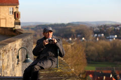 Elderly tourist in a historic town. Senior man wearing winter jacket and cap taking a picture with his camera Stock Images