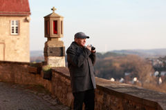 Elderly tourist in a historic town. Senior man wearing winter jacket and cap taking a picture with his camera Royalty Free Stock Photo