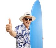 Elderly tourist holding a surfboard and making a thumb up sign Royalty Free Stock Photos