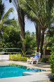 Elderly tourist resting by the pool Stock Images