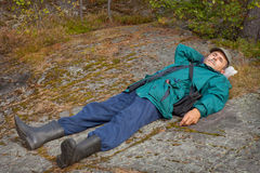 Elderly tourist resting on the rock Royalty Free Stock Images