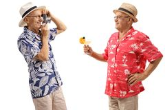 Elderly tourist taking a photo of another elderly tourist with a Royalty Free Stock Photos