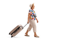 Elderly tourist walking and pulling a suitcase Stock Images
