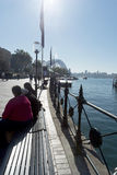 Elderly tourists Circular Quay Winter sun flare Royalty Free Stock Image