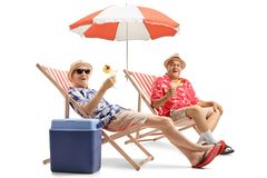 Elderly tourists with cocktails sitting in deck chairs royalty free stock images