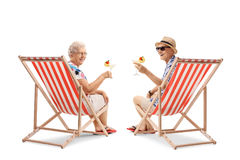 Elderly tourists with cocktails sitting in deck chairs Royalty Free Stock Photos