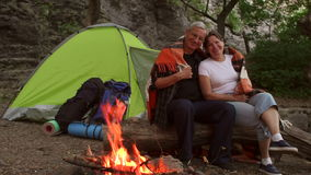 Elderly tourists relax by the fire in the evening. stock footage