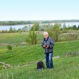 Elderly travel photographer. On the nature Royalty Free Stock Image
