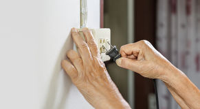 Elderly trying plug cable to the electric outlet Stock Image