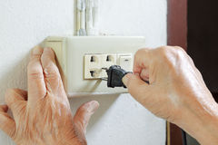 Elderly trying plug cable to the electric outlet Stock Photo