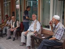 Elderly Turkish men drinking tea. Istanbul, Turkey - September 28, 2015: A group of elderly men sit ourside a cafe drinking their Turkish tea in the Balat Stock Photo