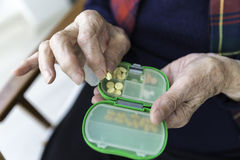 Elderly Turkish woman taking pills from box Stock Photography