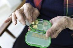 Elderly Turkish woman taking pills from box. Elderly Turkish woman taking pills from green colored medicine box closeup view Stock Photography