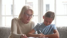 Elderly tutor or grandmother helps schoolchild or granddaughter with homework. Elderly private tutor or grandmother help to schoolgirl or granddaughter with stock footage