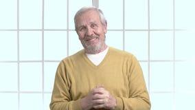 Elderly tv presenter telling the news. Cheerful senior man speaking indoors. Older psychologist at training stock video